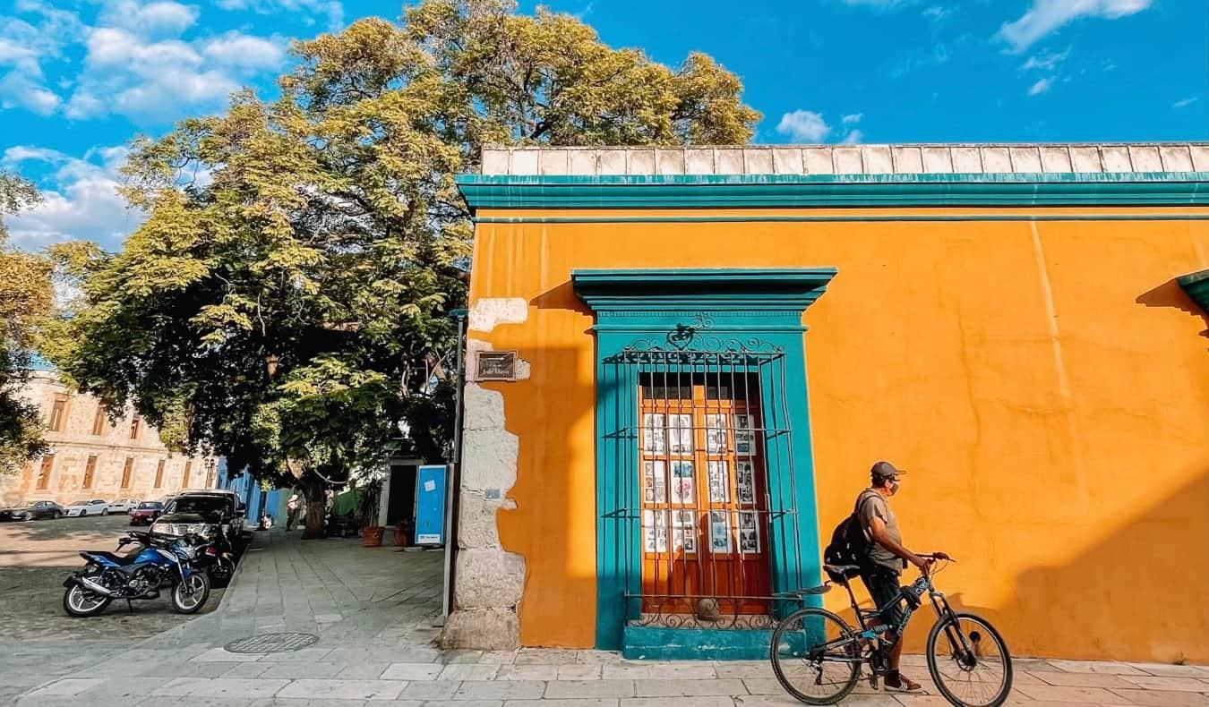 Un homme local à Oaxaca, Mexique avec un vélo près d'un bâtiment coloré