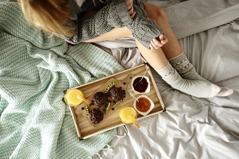Femme méconnaissable et petit déjeuner sur lit