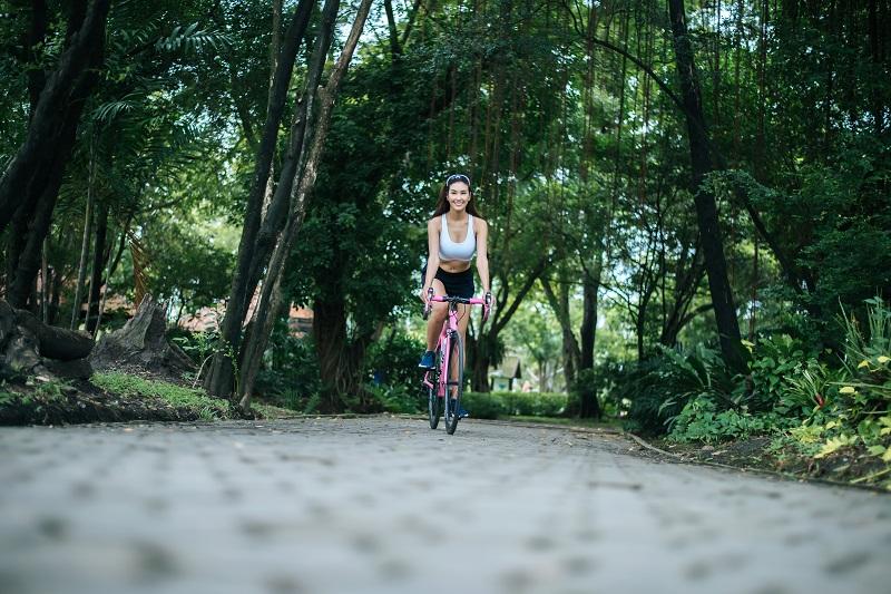 Femme faisant du vélo de route dans le parc.  Portrait de jeune beautifu