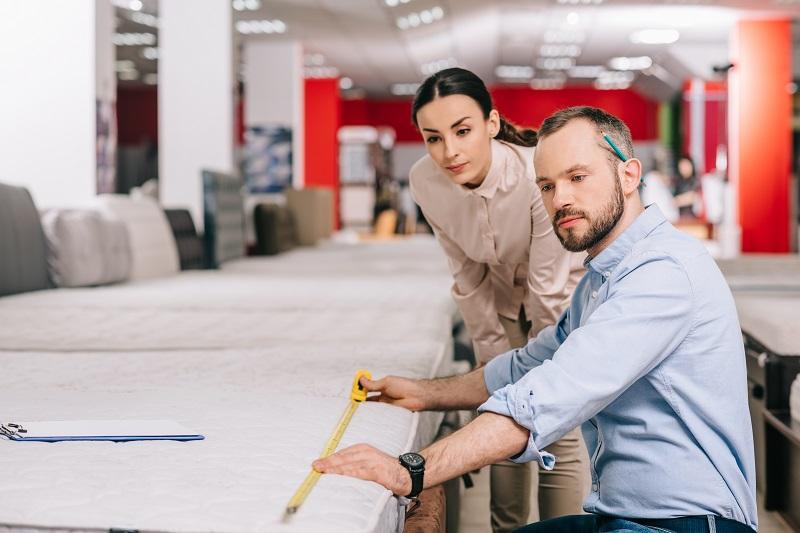 Couple matelas de mesure avec ruban à mesurer dans le magasin de meubles avec matelas arrangés