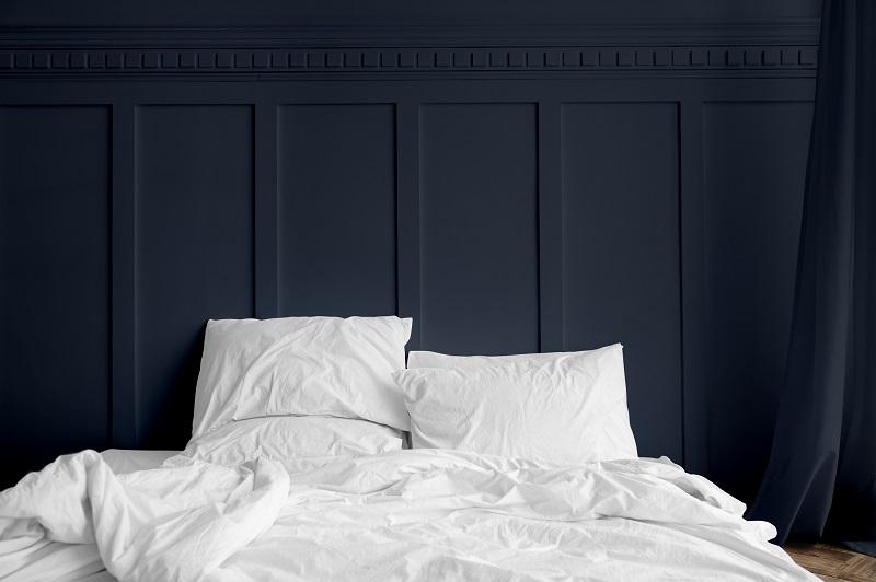 Linge de lit blanc sur un matelas dans une chambre bleu nuit