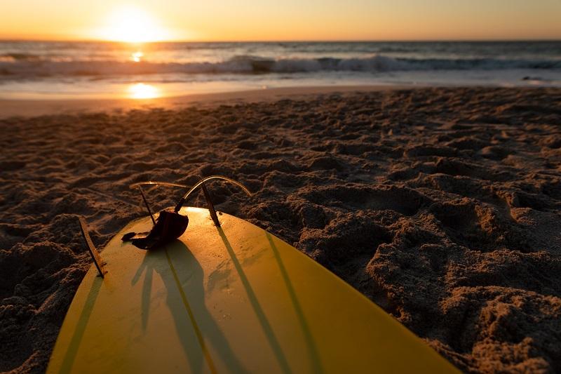 Planche de surf allongé sur une plage de sable avec une mer calme et un ciel clair au coucher du soleil