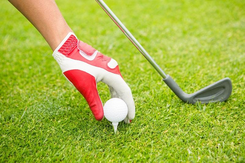 Golfeur plaçant une balle de golf sur le tee au parcours de golf