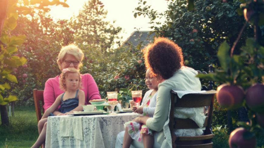 Deux enfants avec deux femmes assises près d'une table en riant