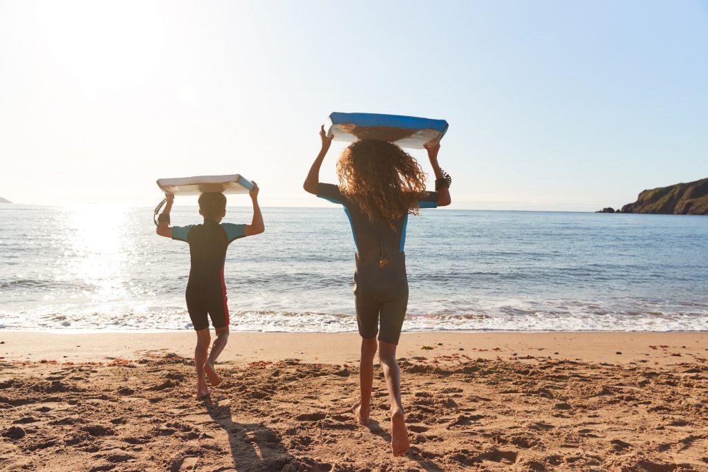 Vue arrière des enfants en combinaisons transportant des bodyboards sur les vacances de plage d'été s'amusant au bord de la mer