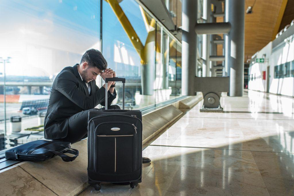 Jeune homme d'affaires en colère contre l'aéroport en attendant son vol retardé avec des bagages