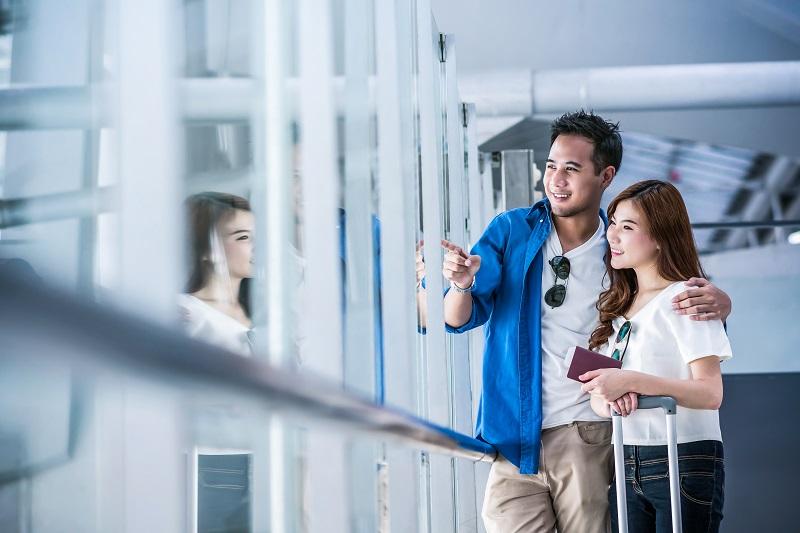 Voyageur couple asiatique tenant le passeport avec des valises à la