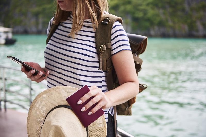 Touriste méconnaissable avec un chapeau et un passeport à la main