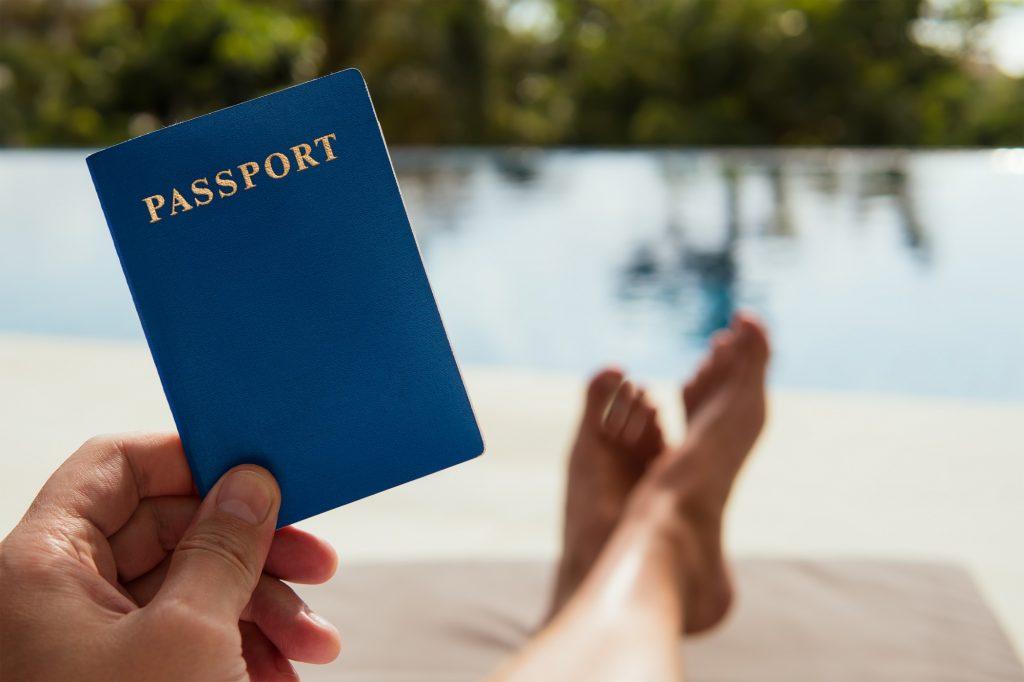 L'homme tient un passeport à la main sur le fond tropical
