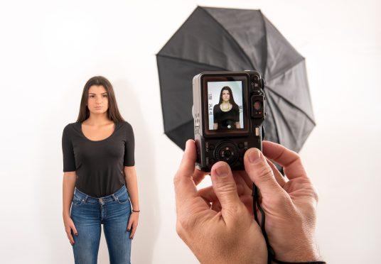 Jolie femme posant pour sa photo d'identité dans un studio photographique avec les mains des photographes au premier plan tenant l'appareil photo avec viseur visible