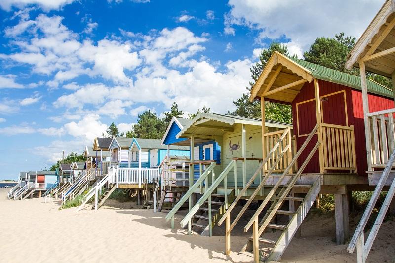 rangée-de-cabanes-de-plage-colorées-sur-une-plage-de-sable-dans-une