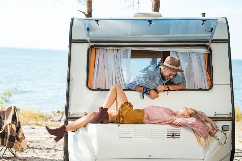 beau couple hippie relaxant sur camping-car près de la mer