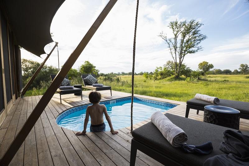 Botswana, un garçon dans une piscine dans un camp de safari, avec vue sur le paysage