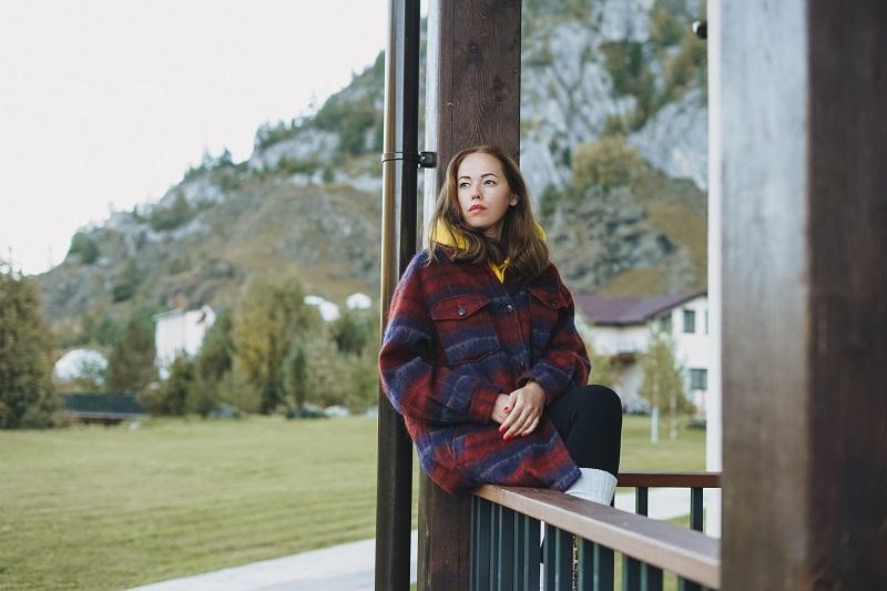 Jeune femme en manteau assis sur une clôture en bois près du chalet sur le fond des montagnes